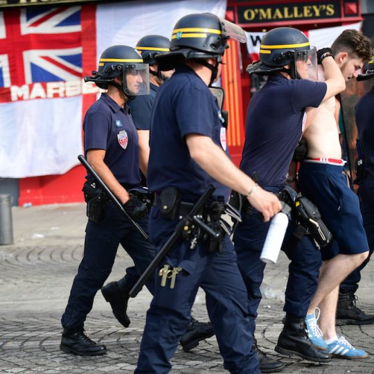 An England fan (2nd R) is detained by police personnel in the port area of the city of Marseille in southern France, on June 10, 2016, ahead of the start of the Euro 2016 football tournament. / AFP PHOTO / LEON NEAL